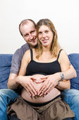 Happy parents make heart sign on pregnant woman's belly on couch — Stok fotoğraf