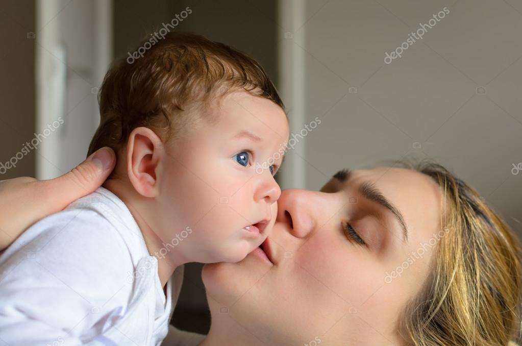 年轻的母亲亲吻她可爱的男婴