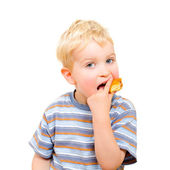 Cute little boy eating delicious cookie isolated on white — Stock Photo