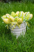 Easter eggs in white pail on grass — Stock Photo