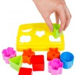 Human hand puts wrong shape into shape sorter toy isolated — Stock Photo #45255607