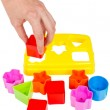 Human hand puts wrong shape into shape sorter toy isolated — Stock Photo #45255611