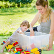 Cute baby boy plays toys with young mother in park — Stock Photo #49139239