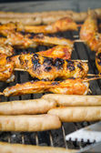 Sausages and chicken wings on smoking grill barbeque — Stock Photo