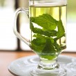 Hot green mint tea standing next to a window with whole mint leaves  — Stock Photo