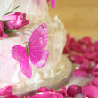Vanilla wedding cake with white icing, rose petals and pink butterflies - Stock Photo