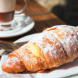 A cup of coffee and fresh cream croissant on a wooden table — Stock Photo #22090795