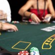 Playing cards, chips and players gambling around a green felt poker table. — Stock Photo #22091083