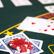 Playing cards, chips and players gambling around a green felt poker table — Stock Photo #22091191