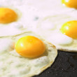 Fresh eggs being fried sunny side up on a large frying pan — Stock Photo #22091281