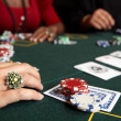 Playing cards, chips and players gambling around a green felt poker table — Stock Photo #22091345