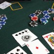 Playing cards, chips and players gambling around a green felt poker table — Stock Photo #22091407