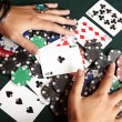 Playing cards, chips and player pulling winnings to herself on a green felt poker table - Stock Photo