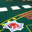Playing cards, chips and players gambling around a green felt poker table — Stock Photo #22091493