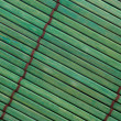 Rough textured green bamboo placemat with brown stitching. — Stock Photo