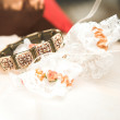 Brown flower bracelet and lace bridal garter lying on a bed — Stock Photo