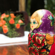Traditional Russian red and purple nested doll or stacking doll on a table - Stock fotografie