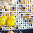 Wire vegetable rack in a kitchen - Stock Photo