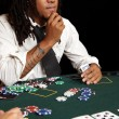 Young African man with dreadlocks playing cards, chips and players gambling around a green felt poker table — Stock Photo #22094743