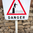Danger sign next to the sea - Stock Photo