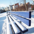 Bench covered in snow in a park in Munch. - Stock Photo