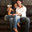 Loving couple on a brown leather couch — Stock Photo