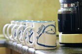 Coffe mugs lined up next to coffee pot — Stock Photo