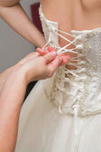 Young bridesmaid helping a bride getting dressed for a wedding — Stock Photo