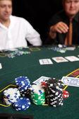 Hrací karty, žetony a hráči her kolem zelené cítil pokerový stůl — Stock fotografie