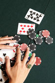 Playing cards, chips and player pulling winnings to herself on a green felt poker table — Stock Photo