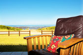 A comfortable leather chair on a patio at a seaside residence or holiday home. — Stock Photo