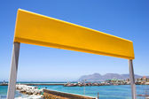 Yellow train station sign against a blue sky with the Kalk Bay harbour — Stock Photo