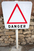Danger sign next to the sea — Stock Photo