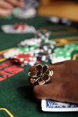 Playing cards, chips and players gambling around a green felt poker table — Stock Photo