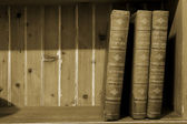 Three old books on a wooden shelf — Stock Photo