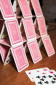 Domeček z karet na dřevěný stůl — Stock fotografie