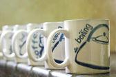 Coffe mugs lined up — Stock Photo