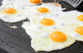 Fresh eggs being fried sunny side up on a large frying pan — Stock Photo
