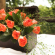 A flower arrangement with red roses and green leaves — Stock Photo