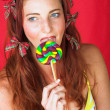 Young female adult fashion model with a big multi-colored lollipop - Stock Photo