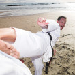 Young adult men practicing Karate on the beach - Stock Photo
