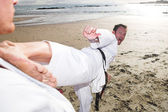 Young adult men practicing Karate on the beach — Stock Photo