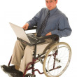 Businessman sitting in a wheelchair working on laptop — Stock Photo #22110085