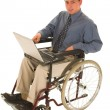 Businessman sitting in a wheelchair working on laptop — Stock Photo