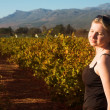 Beautiful blonde woman standing in an autumn vineyard at Boschendal, Western Cape, South Africa — Stock Photo