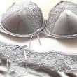 Pair of silver lace lingerie, bra and panties lying on a bed - Stock Photo