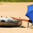 Man relaxing on the beach under a blue umbrella with boat — Stock Photo #22116067