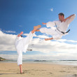 Young adult men with black belt practicing on the beach — Stock Photo