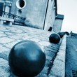 Iron balls and building in the background in Antibes, France. - 图库照片