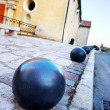 Iron balls and building in the background in Antibes, France. - Stock Photo